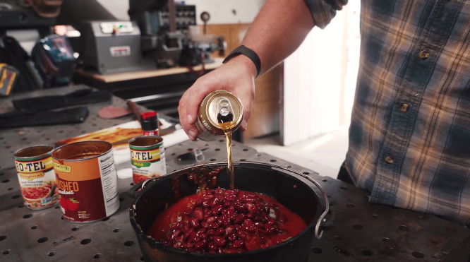 john malecki pouring beer into chili