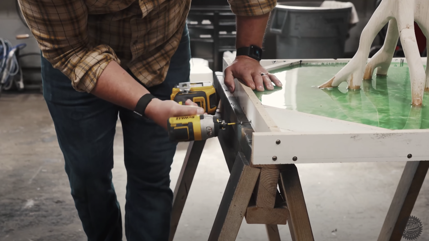 man drilling screws into epoxy project