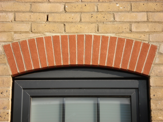 Brick slip arch above door with brick wall