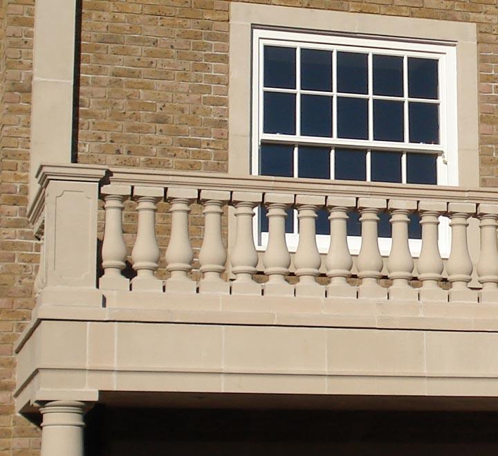 Cast stone balcony ledge with window and brick wall