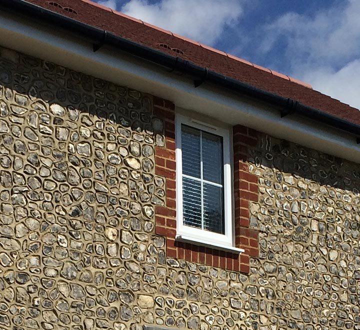 Handcrafted knapped walling flint with window and house roof