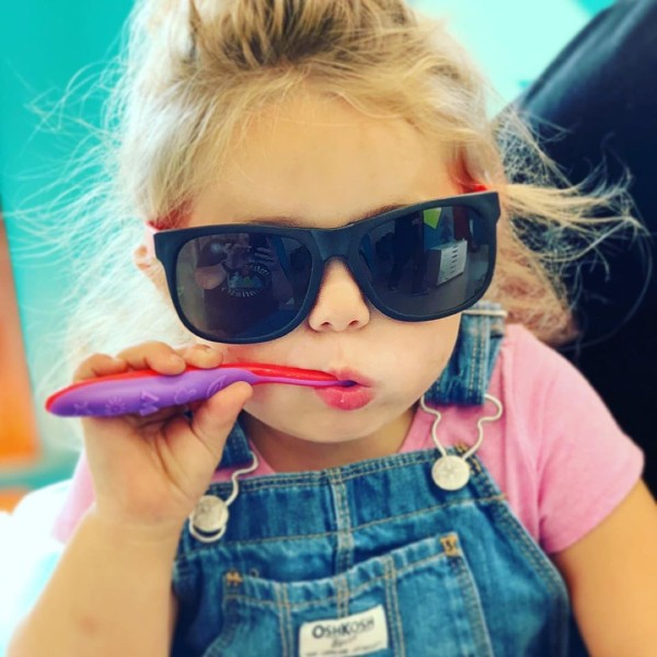 a little girl wearing sunglasses with a toothbrush