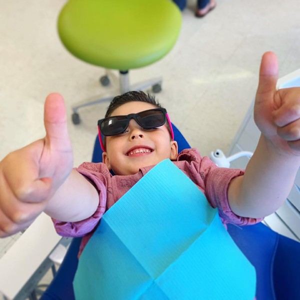 a kid with sunglasses smiling in dental chair