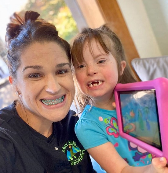 a dental hygienist smiling with girl patient