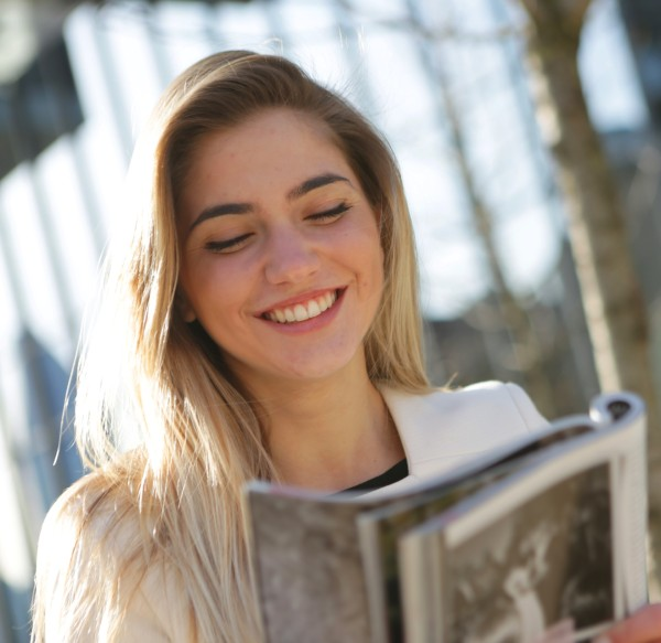 a teenager girl reading and smiling