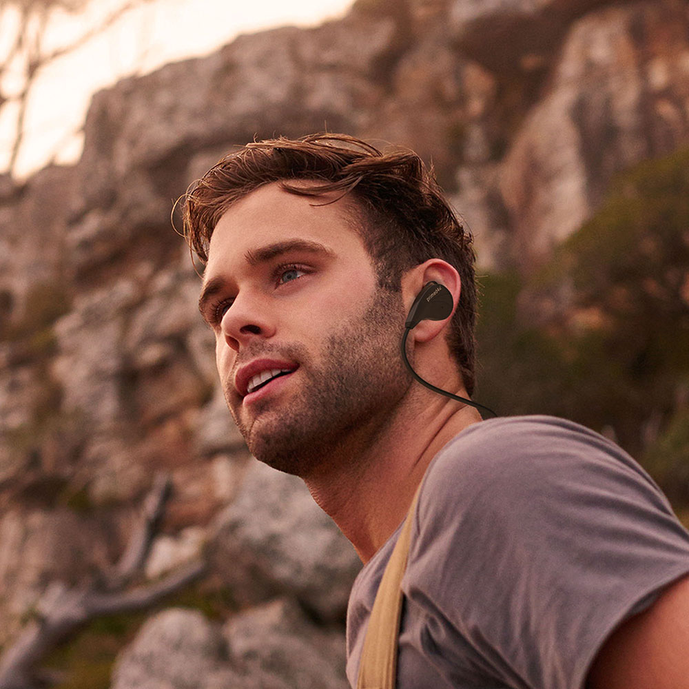 Young man hiking with Primed4U's headphones