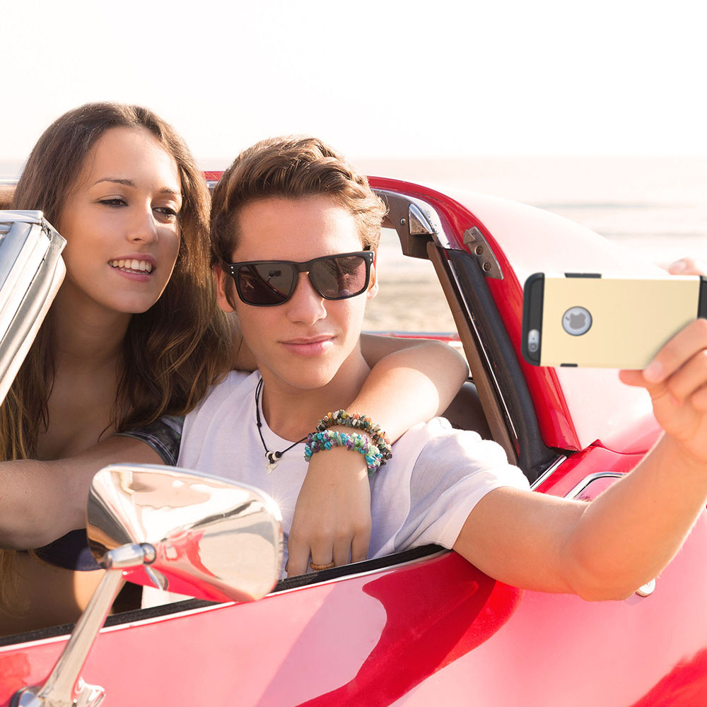 Teenagers in red car outside taking a photo of themselves