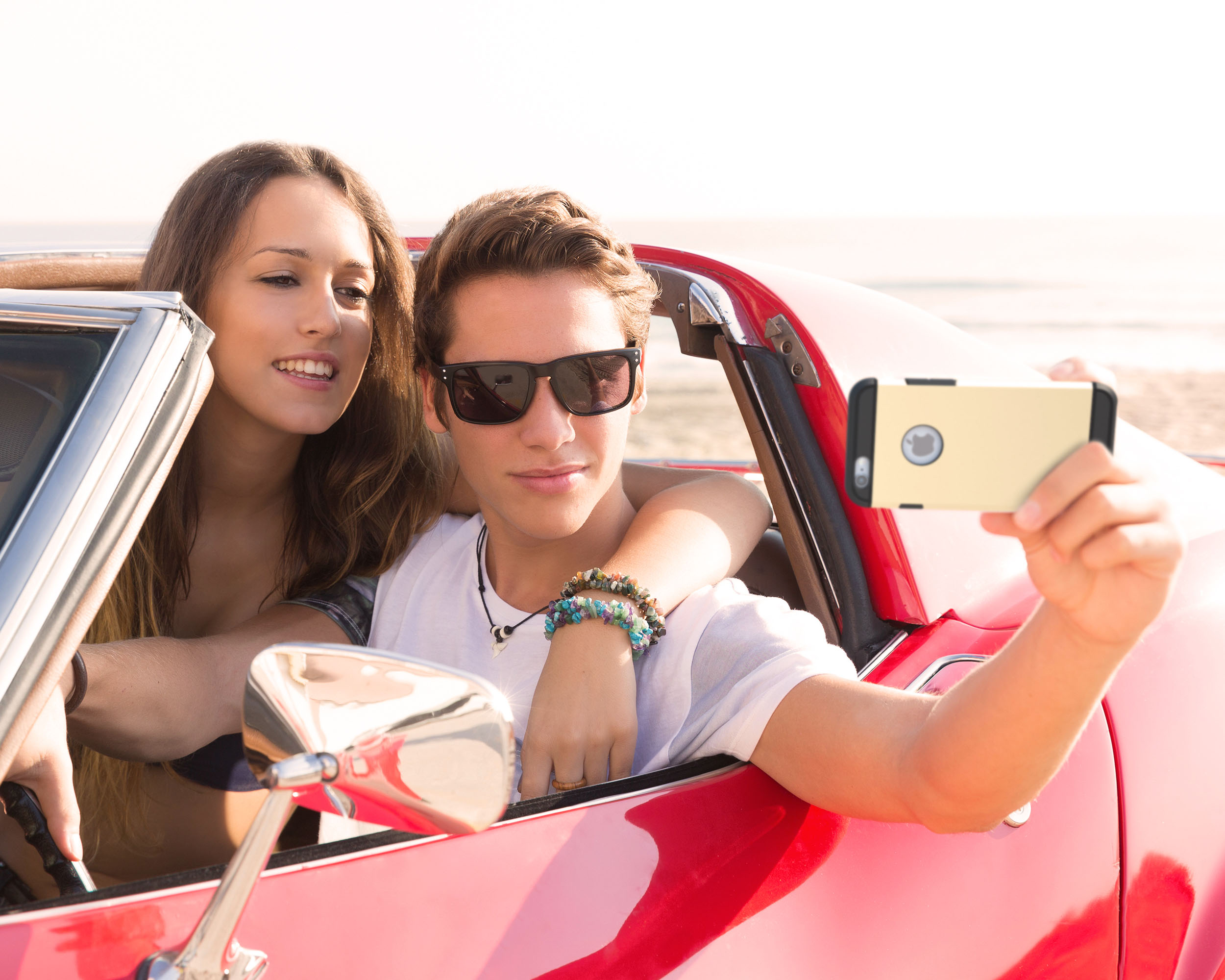 Teenagers in red car holding phone and taking pictures of themselves