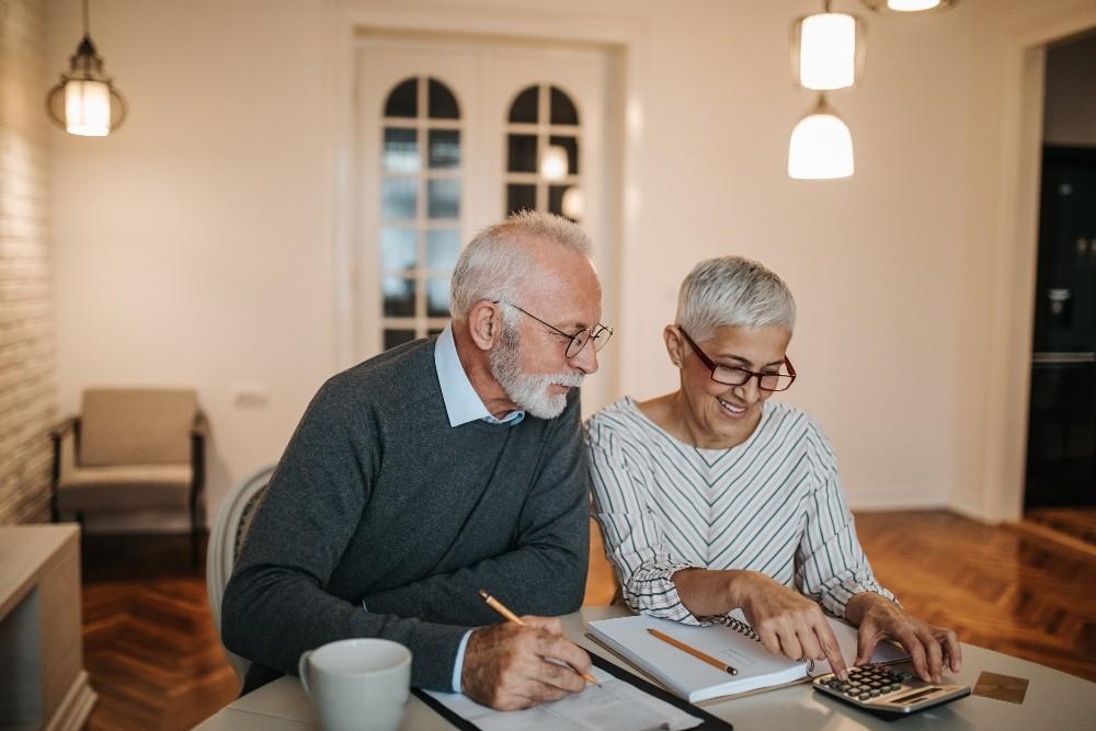 elderly couple signing documents