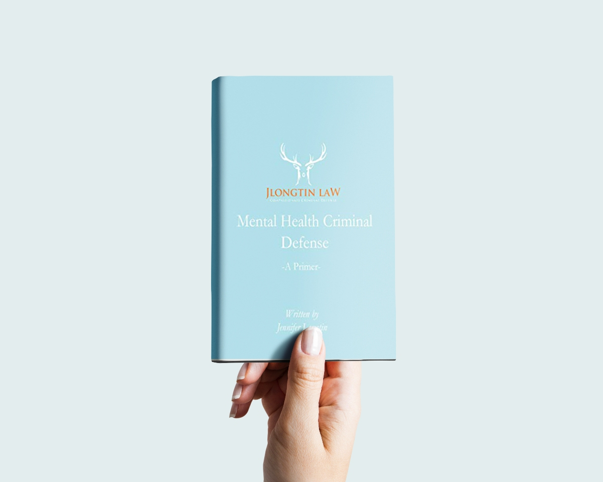 Hand holding a copy of the book Mental Health Criminal Defense: A Primer