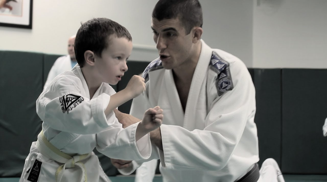Child learning bully prevention using Brazilian Jui-jitsu being taught by Rener Gracie