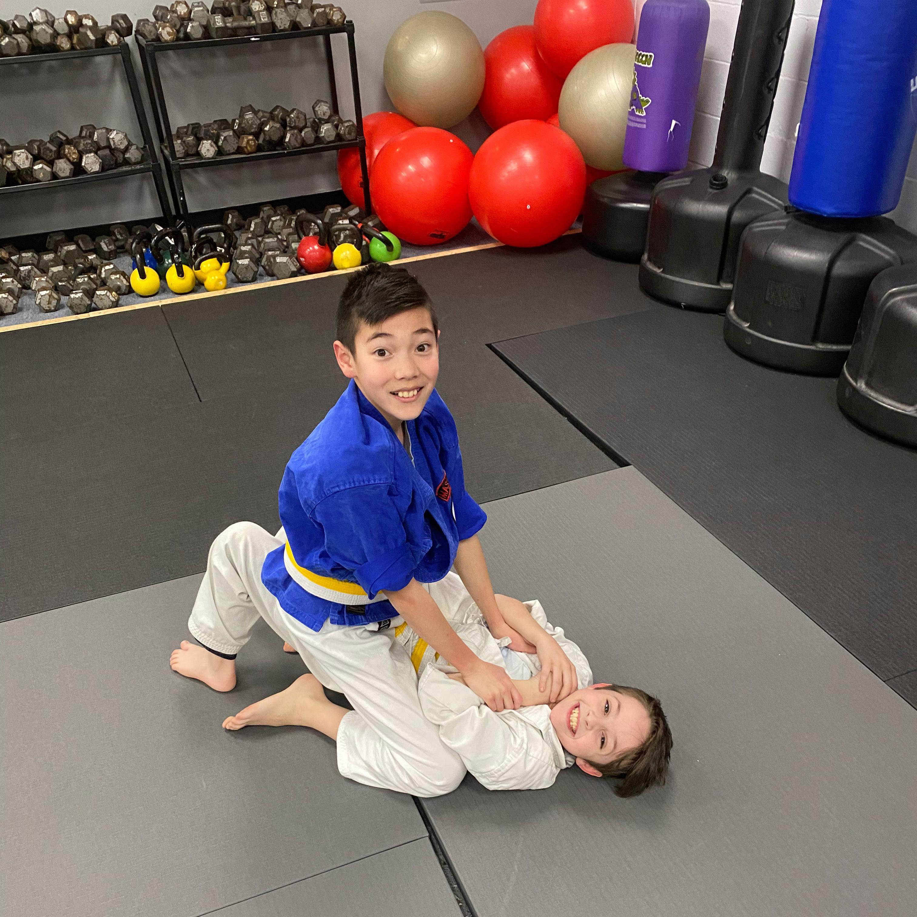 Two kids having fun and learning juijitsu