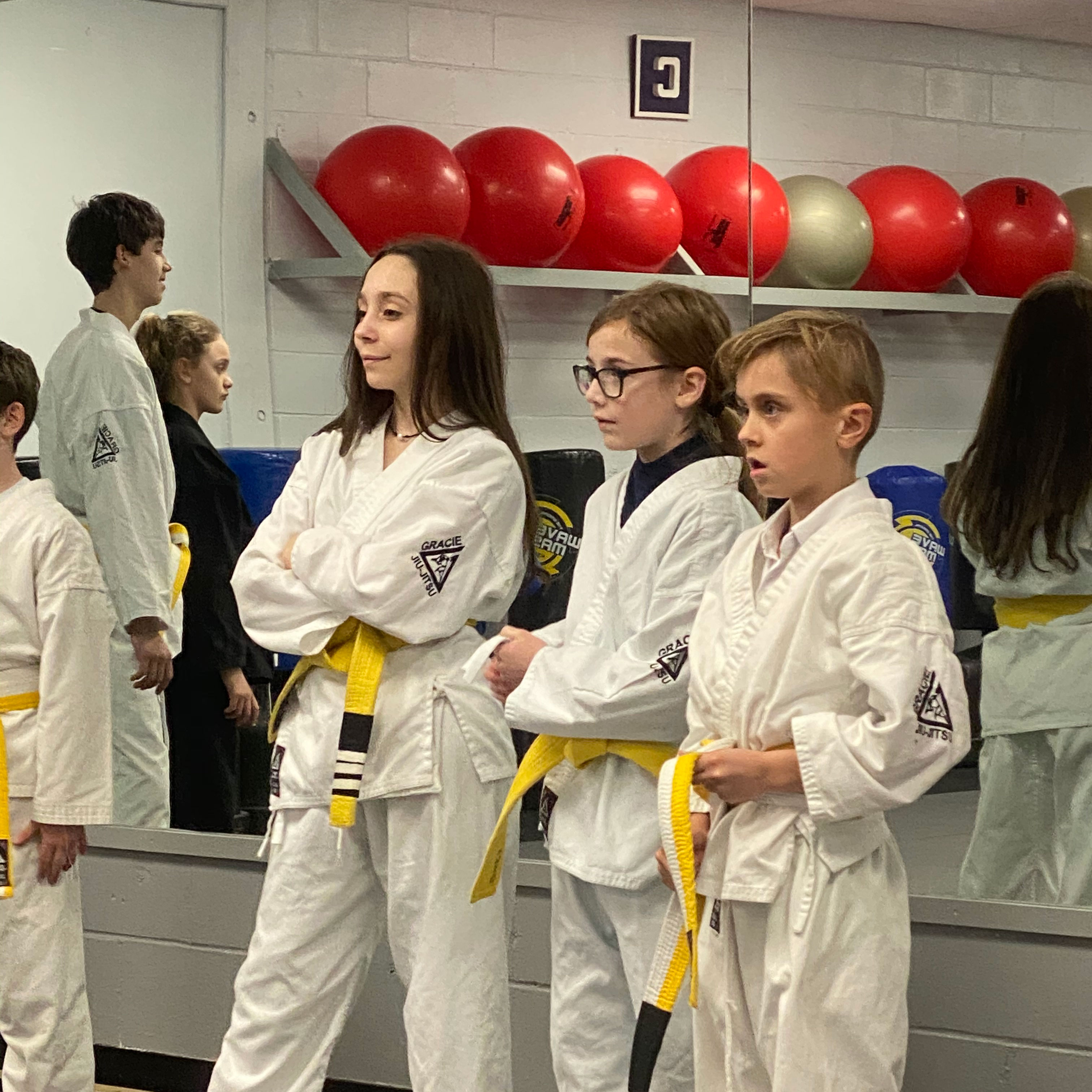 Three children in karate uniforms watching juijitsu class