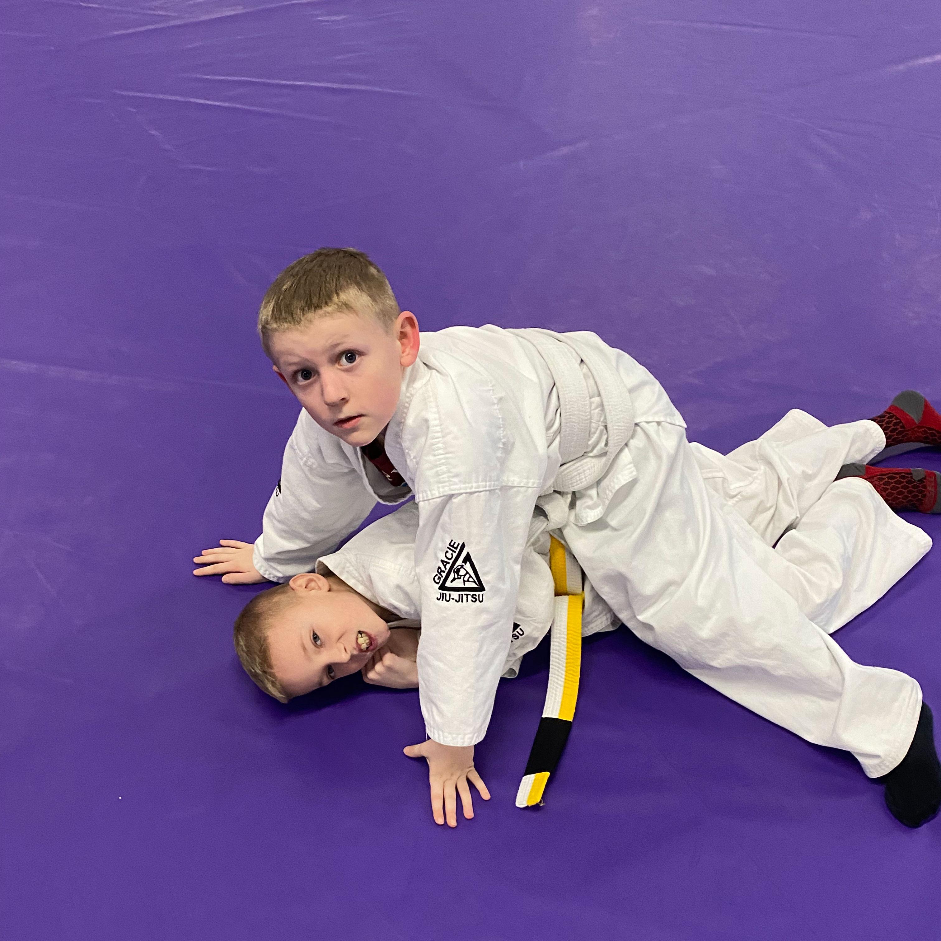 Two children practicing juijitsu techniques