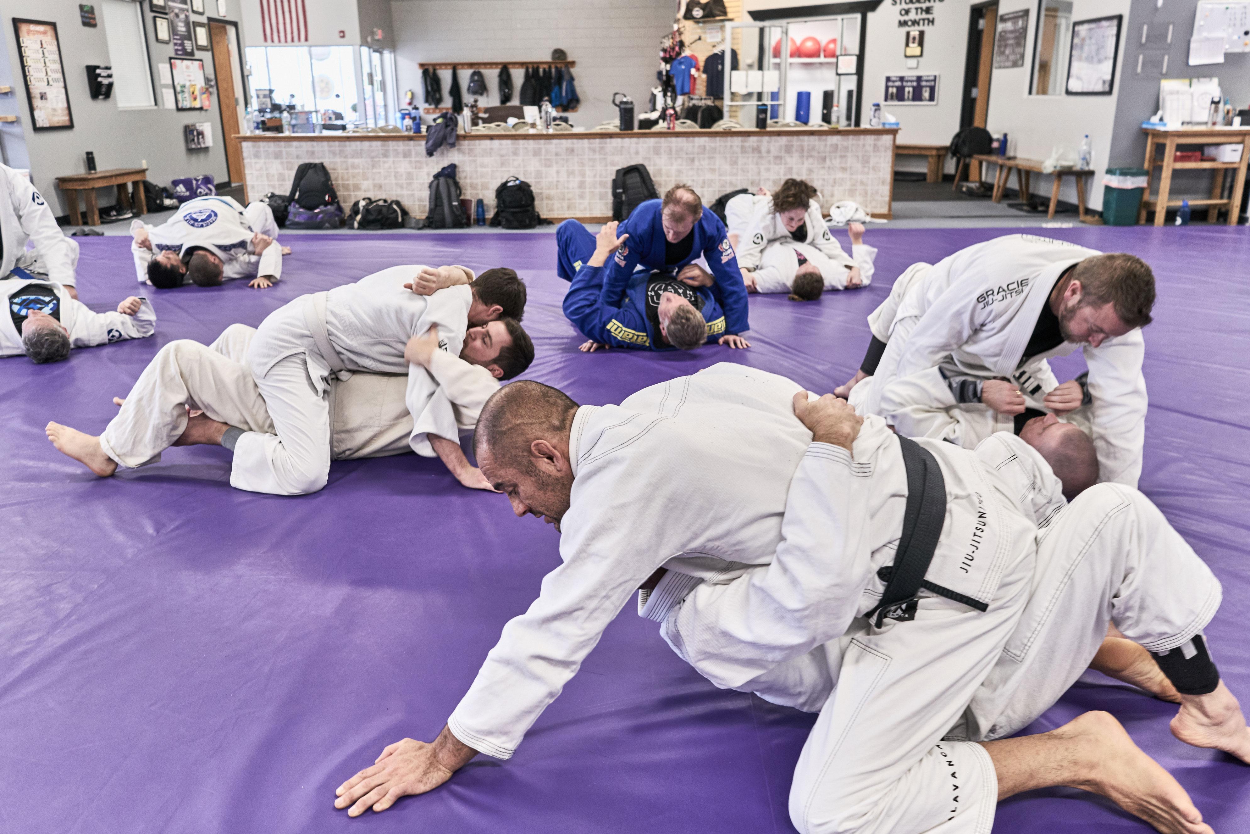 Black belt jui jitsu instructor working with student during seminar