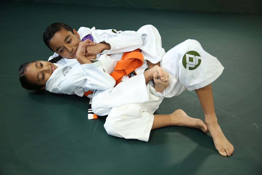 Juijitsu instructors demonstrating sparring techniques to kids martial arts class
