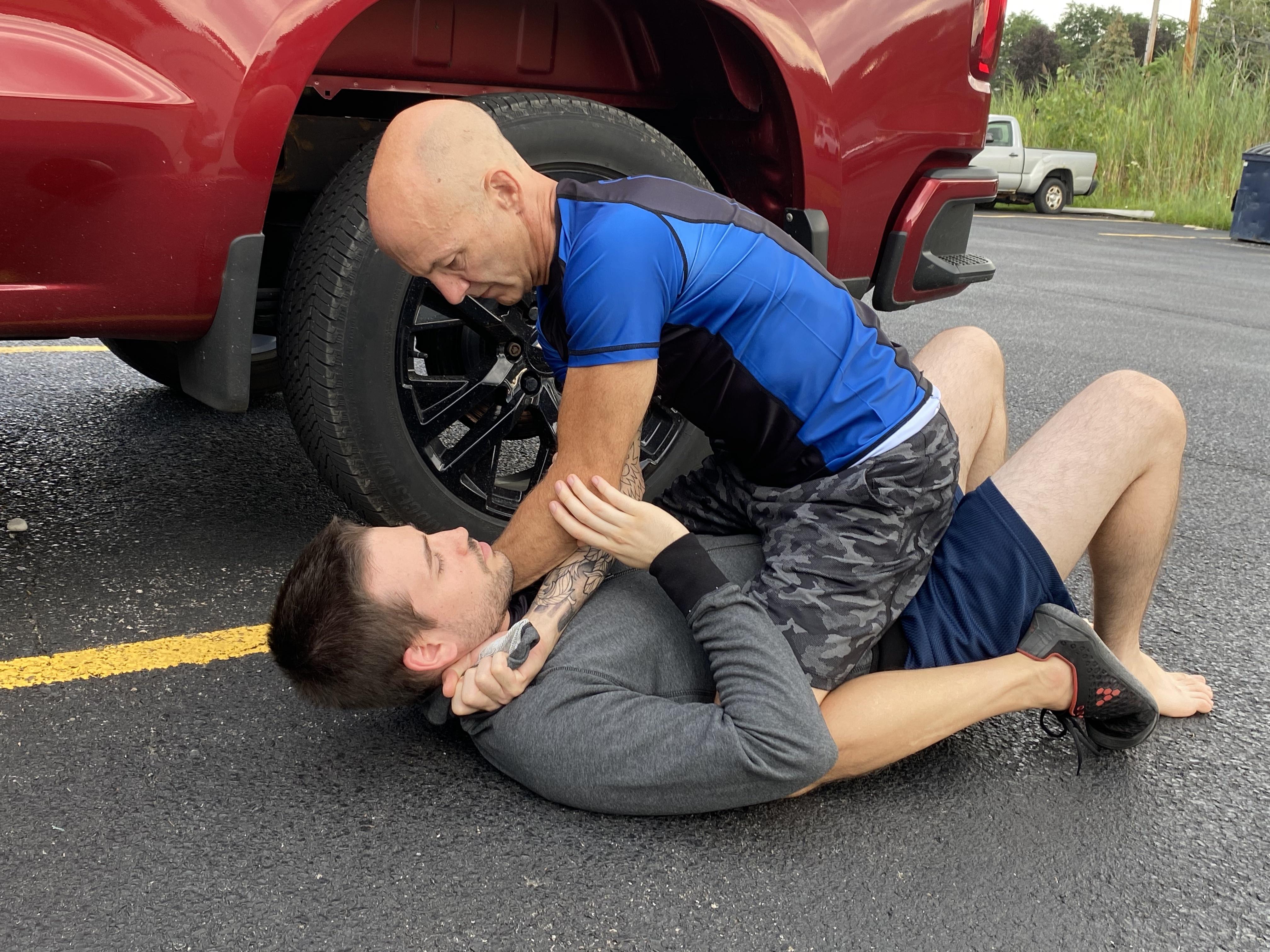 Woman practicing self-defense techniques against male attacker using Gracie jui jitsu