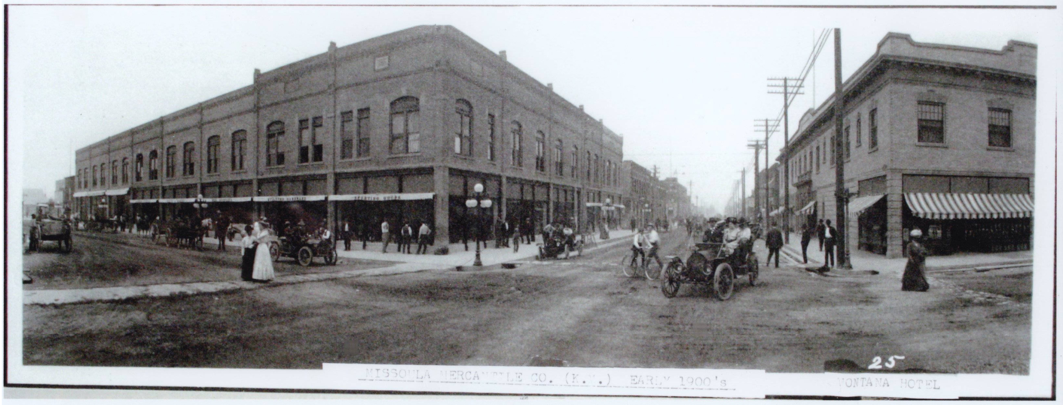B and W wide angle photo of 2nd St looking west from 1st Ave East. The Missoula Mercantile Co., later (1911) known as the Kalsipell Mercantile Co., is on the left (SW corner) and the Montana Hotel right (NW corner) in the photo. Numerous people walking or riding bicycles. There are a mix of horse drawn wagons as well as early model automobiles. Caption reads, 'Missoula Mercantile (K.M.) Early 1900's. Montana Hotel.' The Montana Hotel was built in 1909.