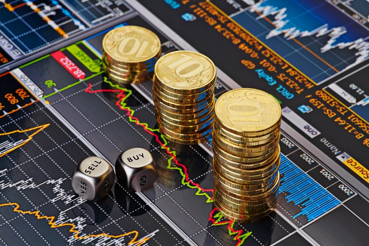 Pilhas de moedas e dois dados sobre uma tela com gráficos coloridos de preços de ações e títulos