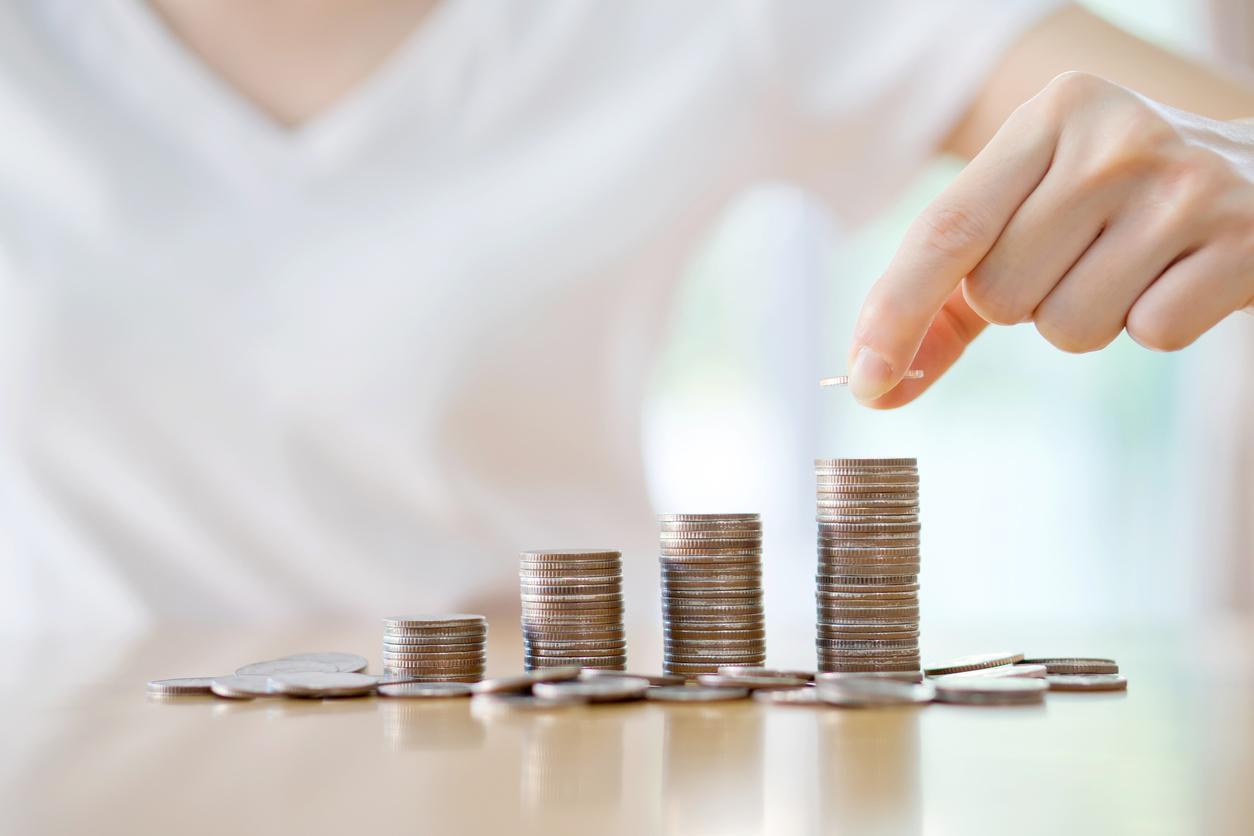 Mulher empilhando moedas em 4 pilhas de forma crescente