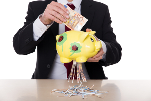 Homem de terno colocando uma nota de euro em um porco e a nota saindo rasgada
