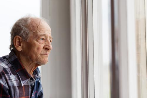 Idoso preocupado com o olhar distante em frente a uma janela