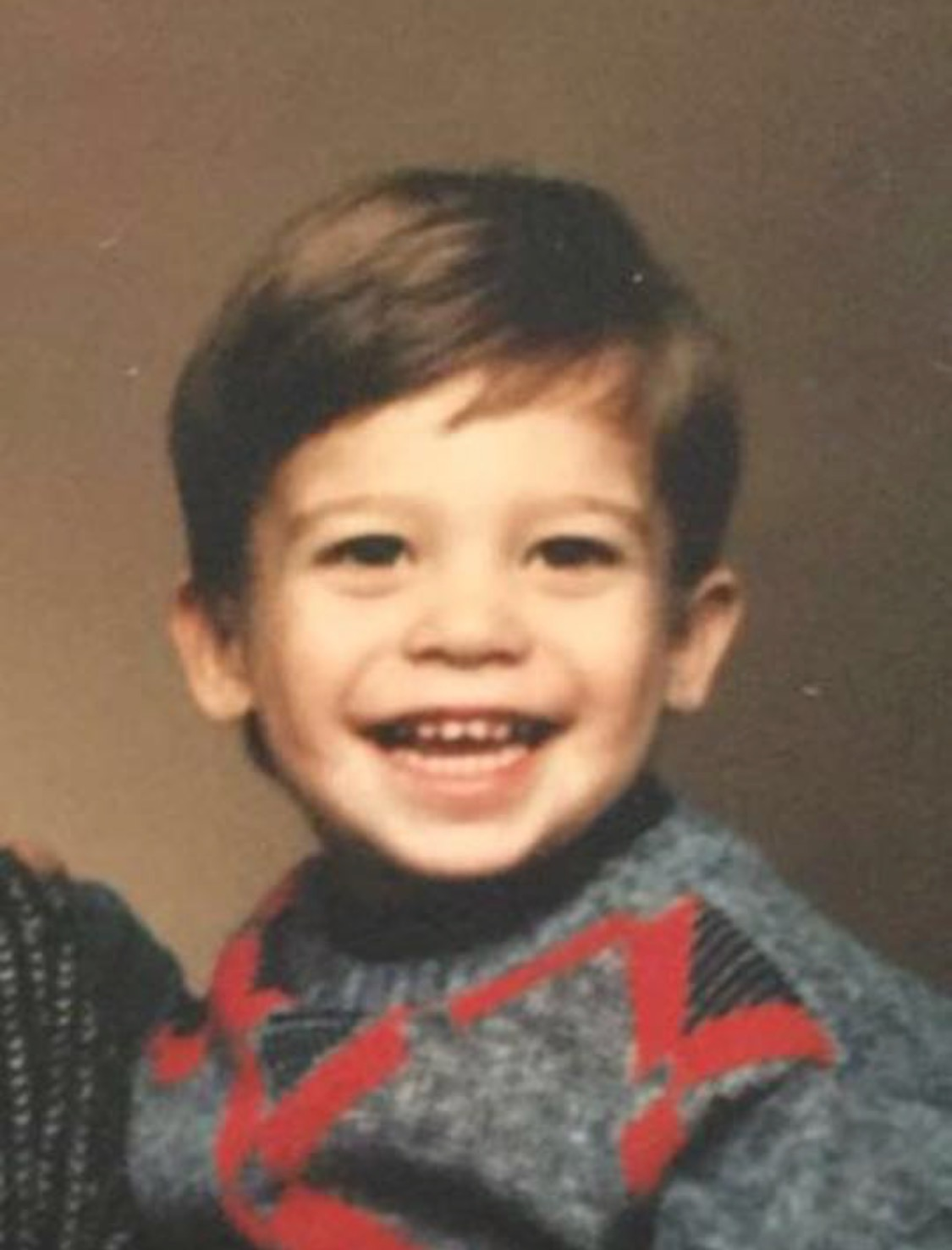 Mike Dewey as a kid, cheesing for the camera in his sweater