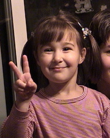 Jessica Livak as a kid, throwing up a peace sign to the camera