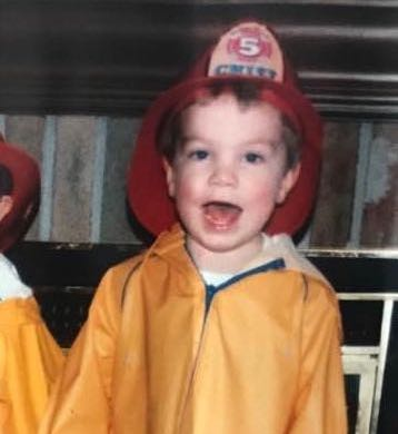 Randall Brown as a kid, wearing a firefighter's uniform and smiling