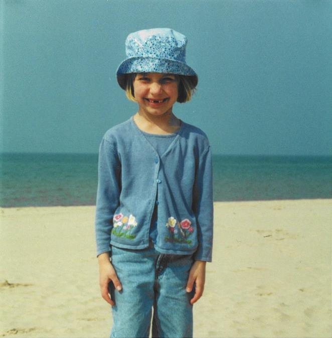 Carlie Penning as a kid, standing awkwardly in front of a lake on the beach