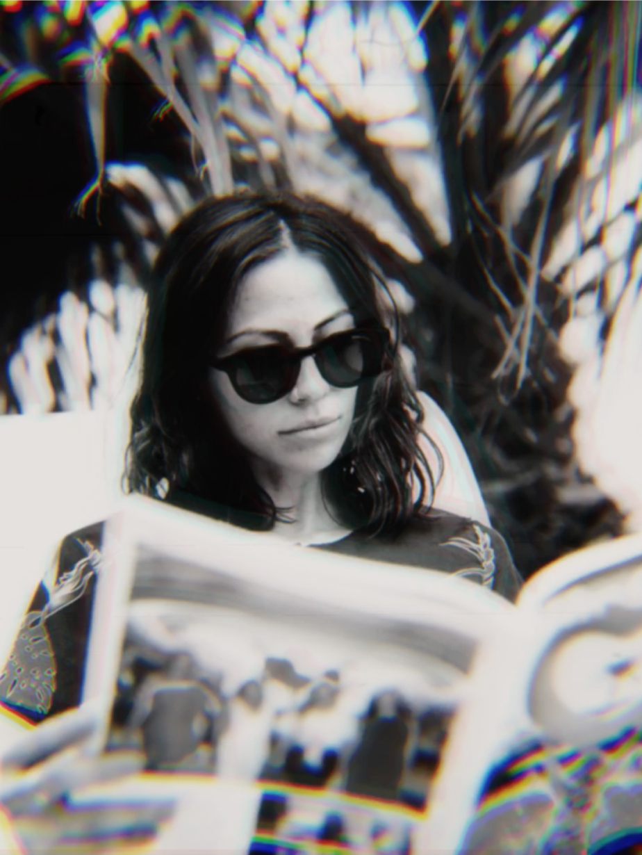 A girl with sunglasses on reads a magazine in Palm Springs, filtered with Niles' Chromatear look