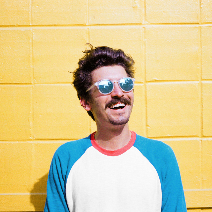 Adam smiles in sunglasses against a bright yellow wall
