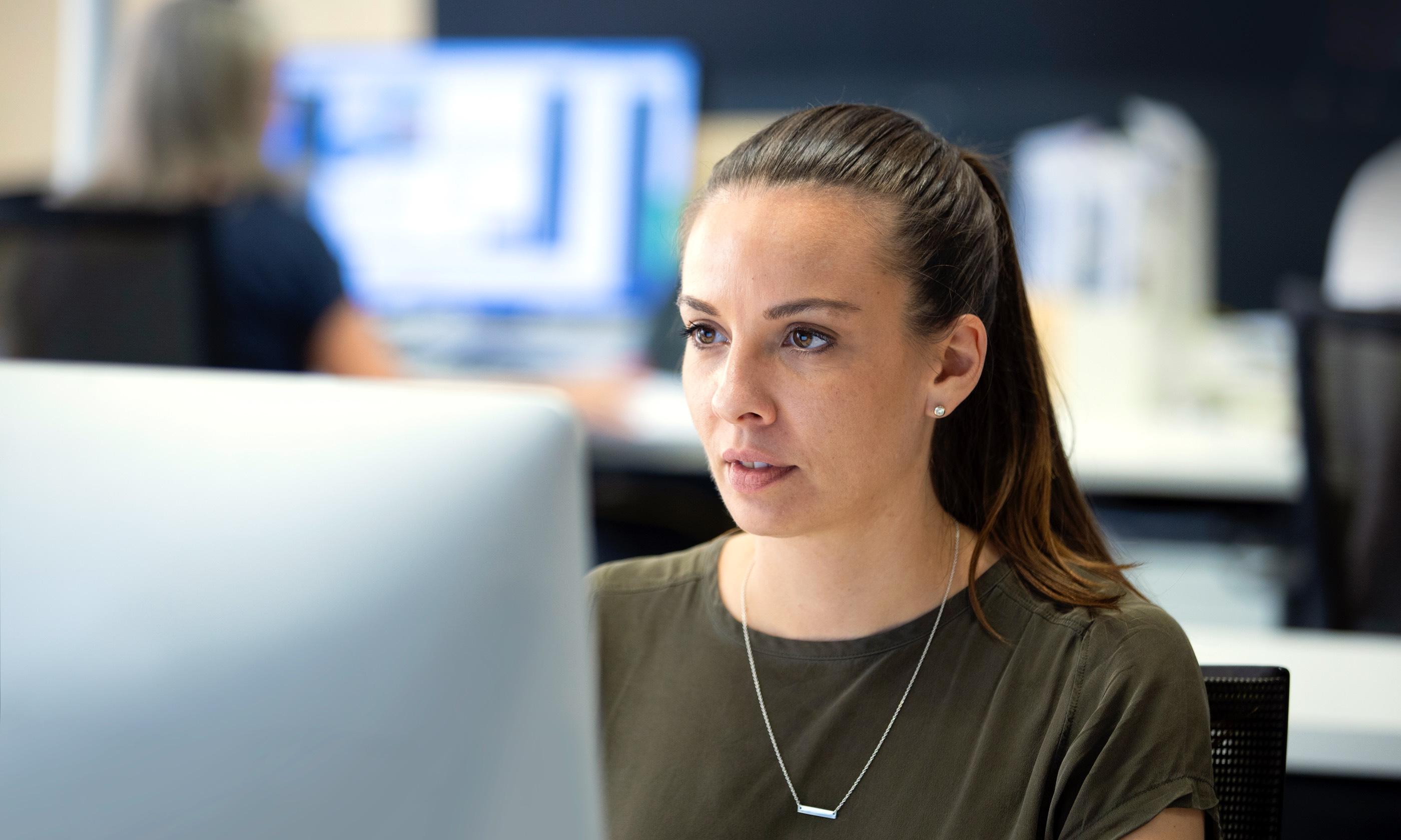 Designate team member working in studio at computer.