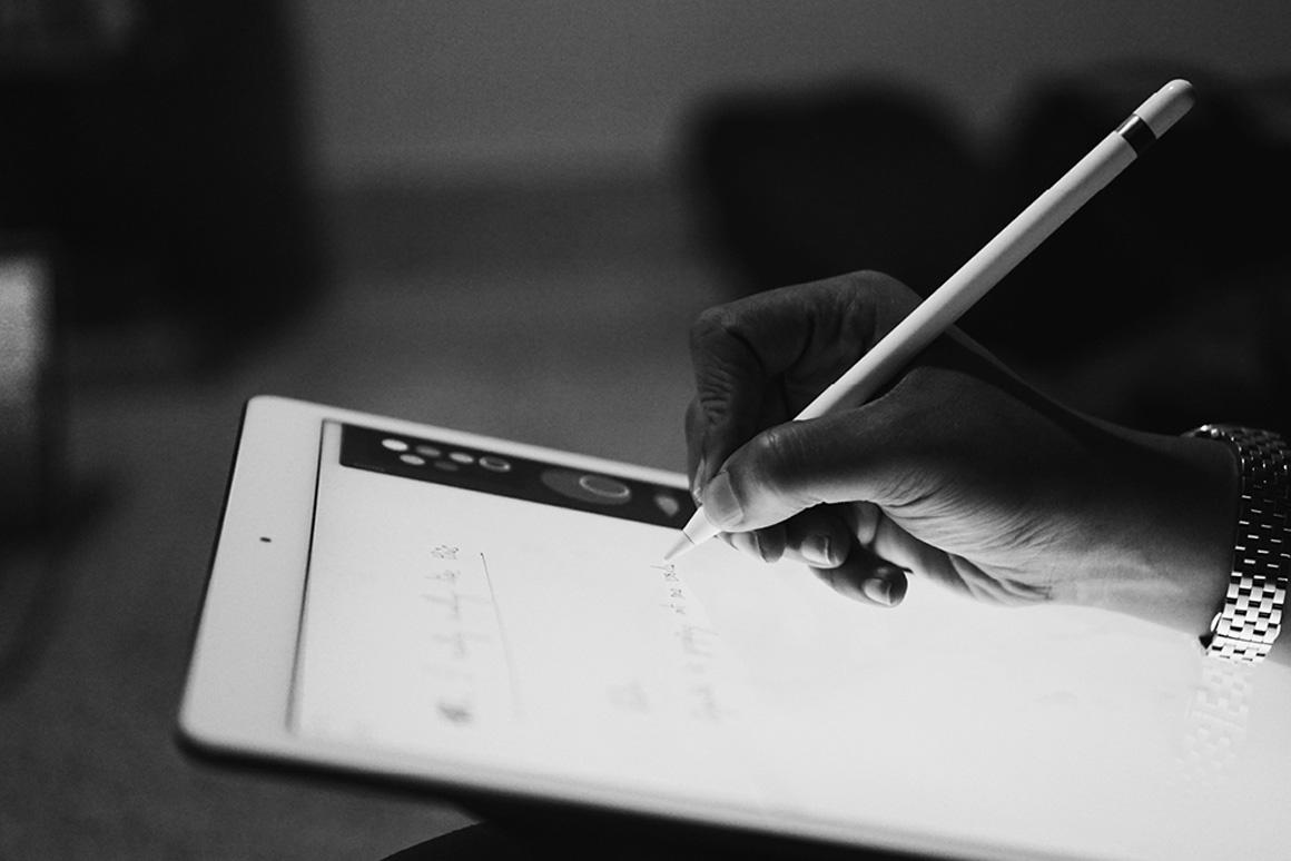 Designate team member taking notes on tablet.