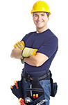 A smiling worker with arms crossed, a yellow hard hat and a tool belt