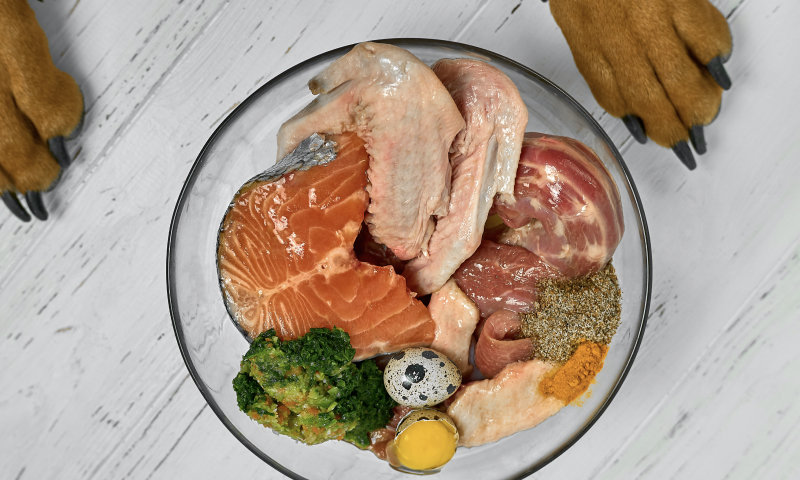 Raw chicken salmon and beef in a glass bowl with broccoli quail egg and spices