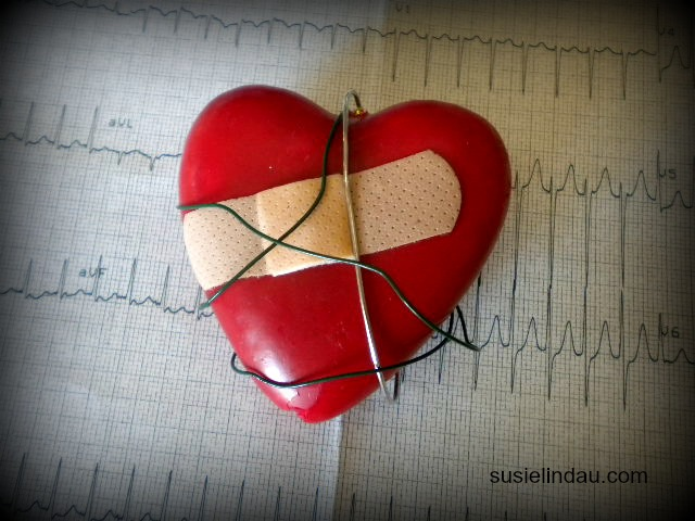 Red plastic heart with bandaid on top ECG chart