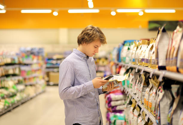 Man wearing blue collared shirt reading product information and also using smartphone in pet food aisle at a pet sotre