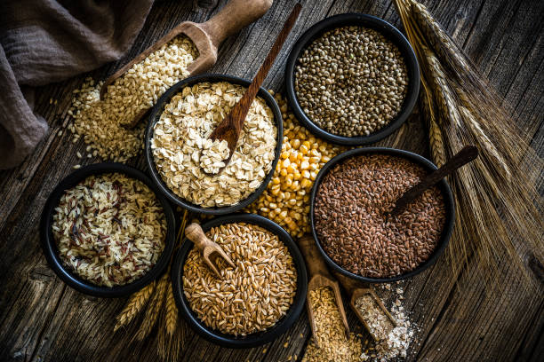Large group of wholegrain food shot on rustic wooden table Top view of wholegrain and cereal composition shot on rustic wooden table. This type of food is rich of fiber and is ideal for dieting. The composition includes oat flakes, brown rice, dried corn,spelt, hemp seeds and flax seeds. Predominant color is brown. XXXL 42Mp studio photo taken with SONY A7rII and Zeiss Batis 40mm F2.0 CF fibre stock pictures, royalty-free photos & images