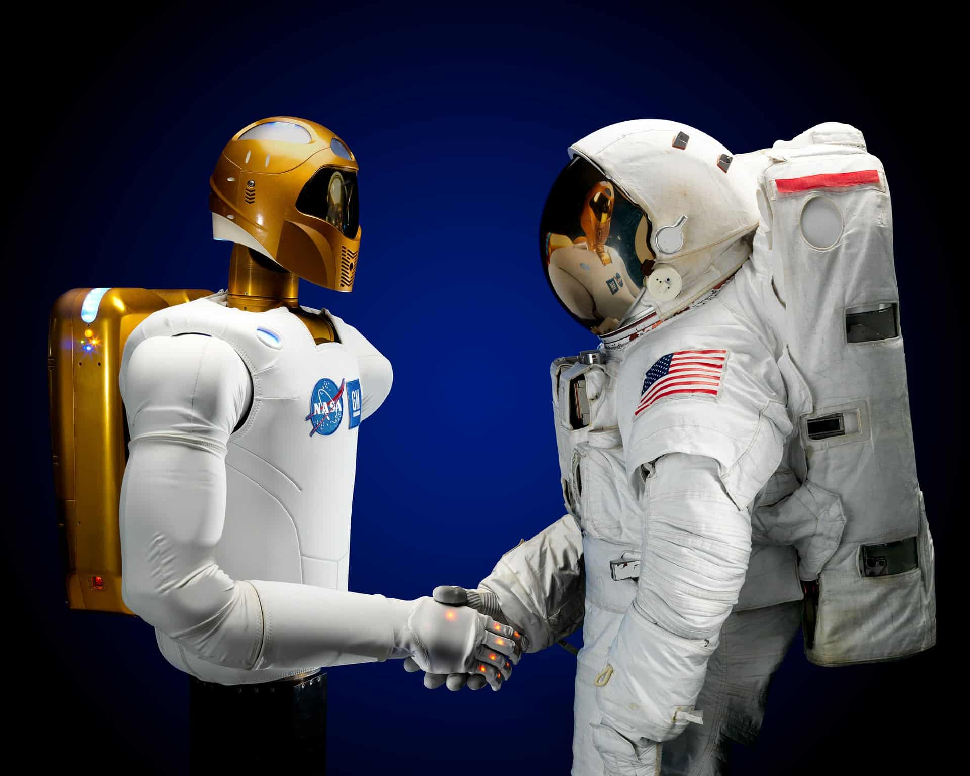 Image of a modern NASA astronaut shaking hands with old school astronaut.