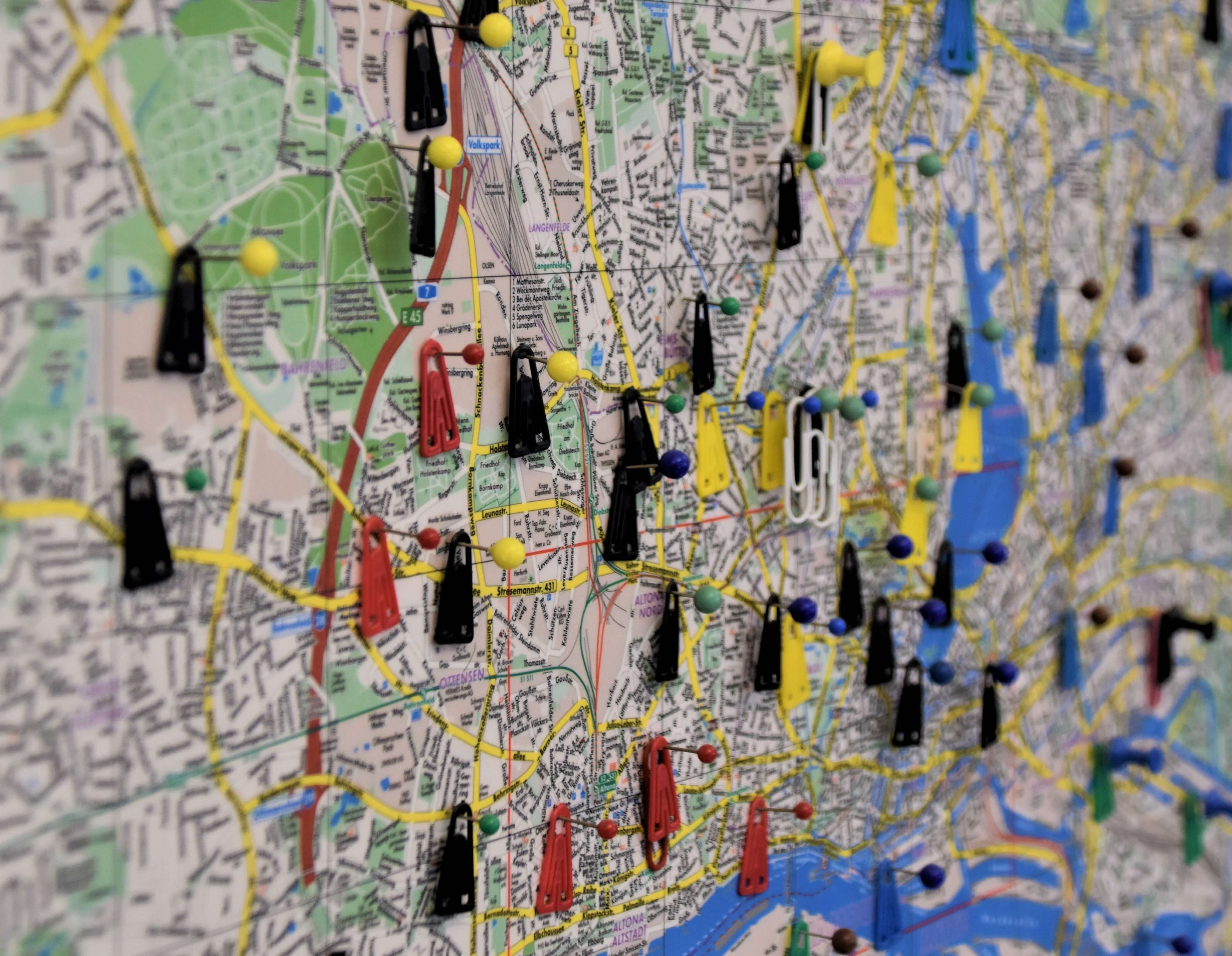 Map with yellow, black, and red pins in it.