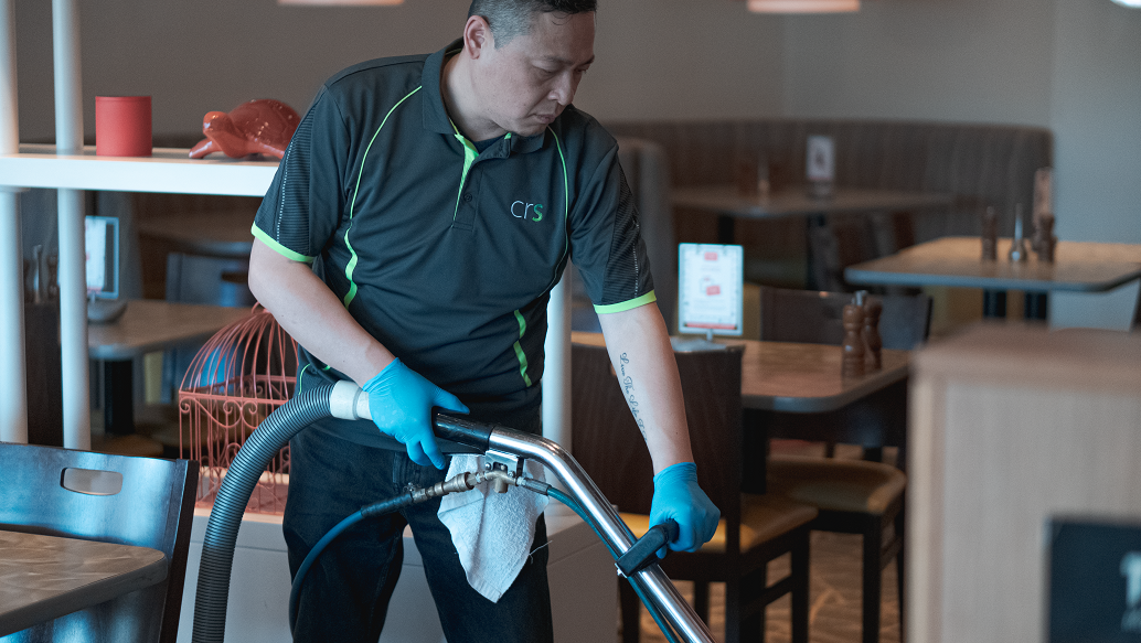 Employee hot water extracting the carpets of a restaurant