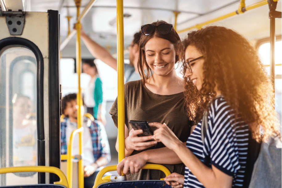 Girls on public transport looking at mobile phone answering survey.