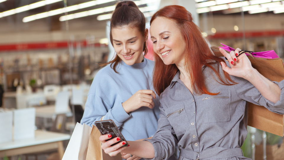 Mother and daughter looking at survey on smartphone while shopping.