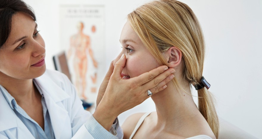 Doctor looking at a woman's nose in an office setting.