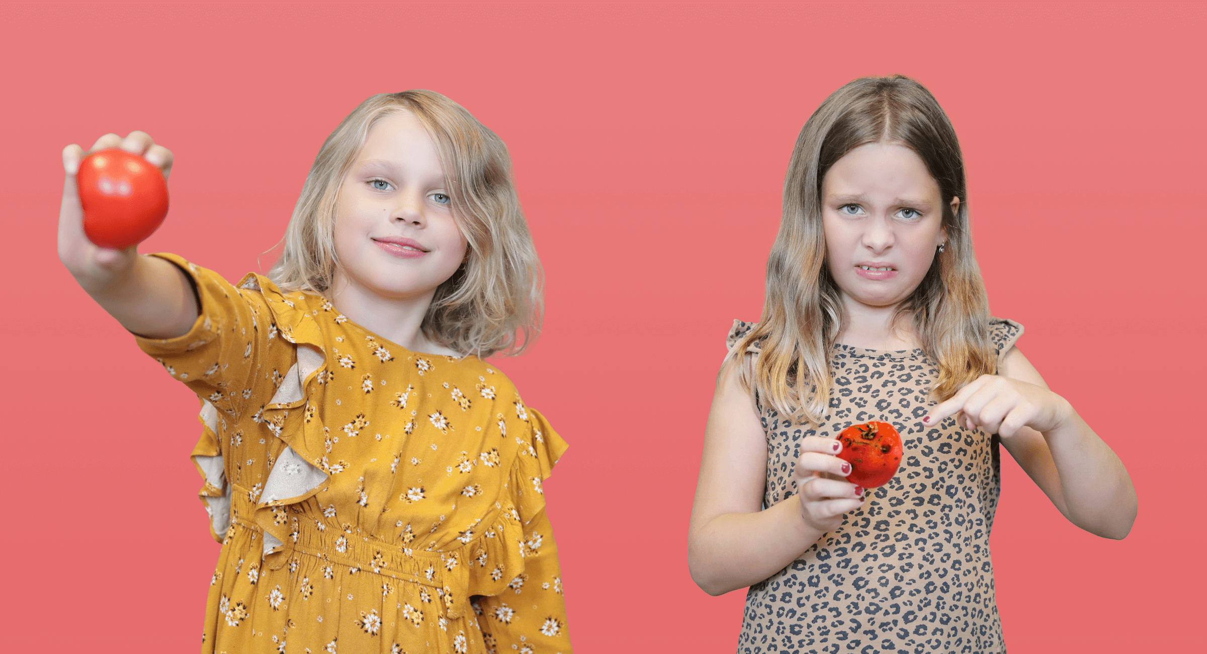 One girl holds a fresh tomato and looks confident. The other girl holds a rotten tomato and looks dissatisfaction.