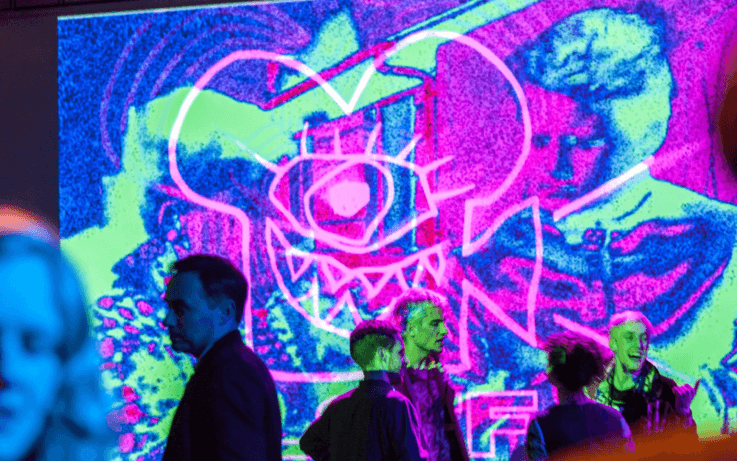 Colourful projection on wall people walking in background