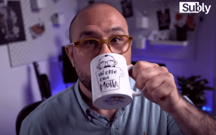 man drinking coffee from mug with un cafe con motta written on it