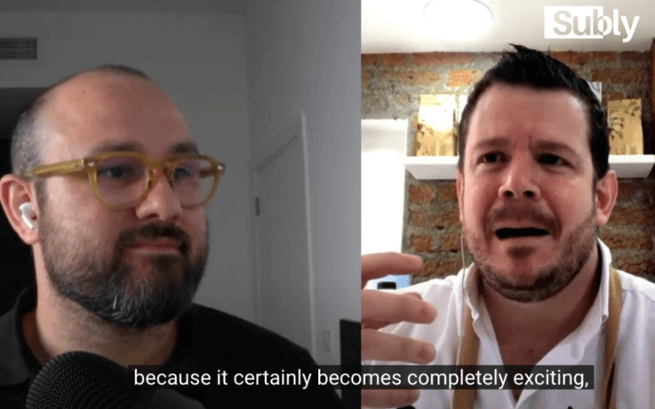 two men talking side by side on zoom call with subtitles on screen