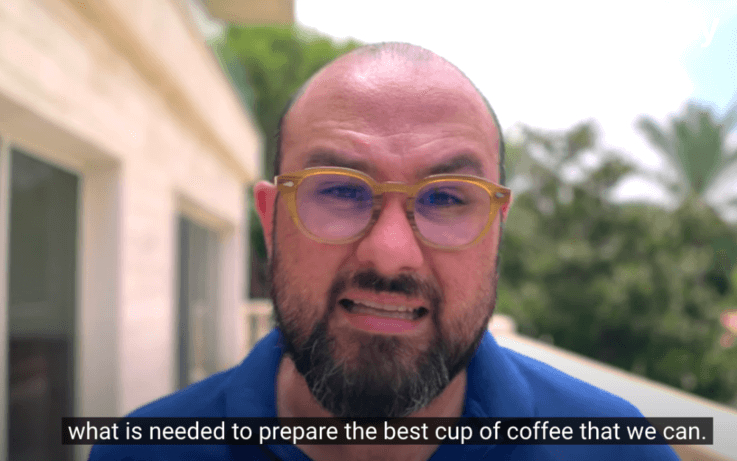 man speaking to camera outside in sunshine with subtitles on screen